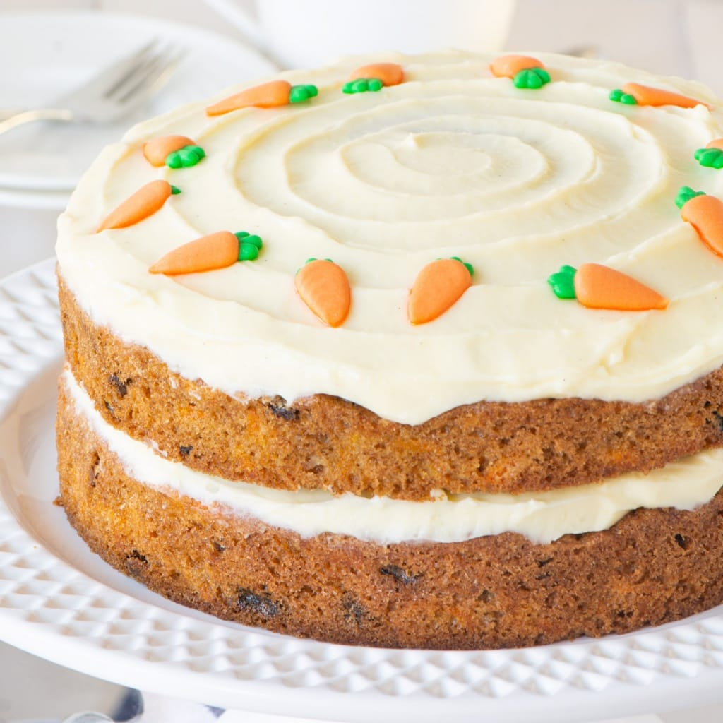 Carrot cake topped with cream cheese buttercream and decorated with sugar carrots.