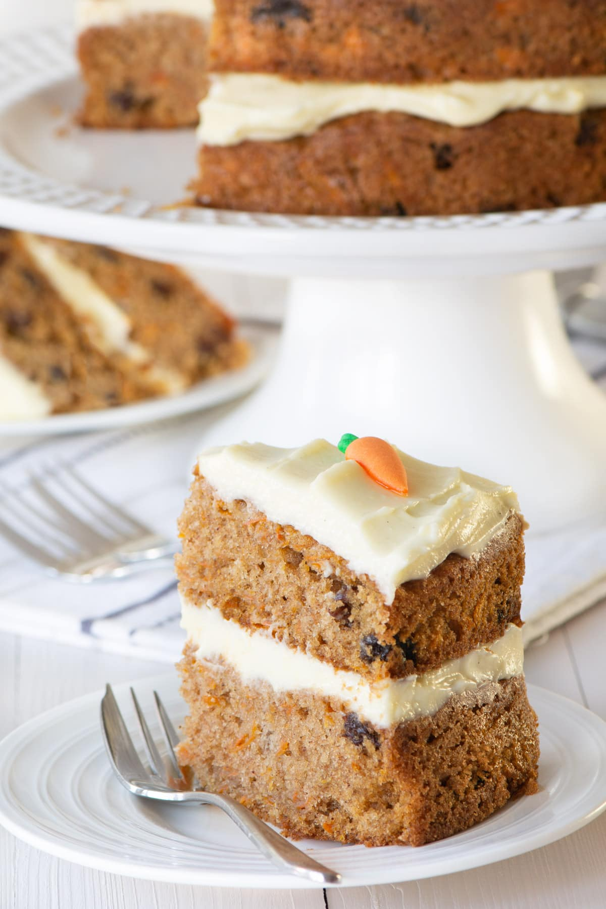 A slice of carrot cake on a white plate. The remaining cake is in the background. The slice shows the raisins running through the carrot cake sponge.