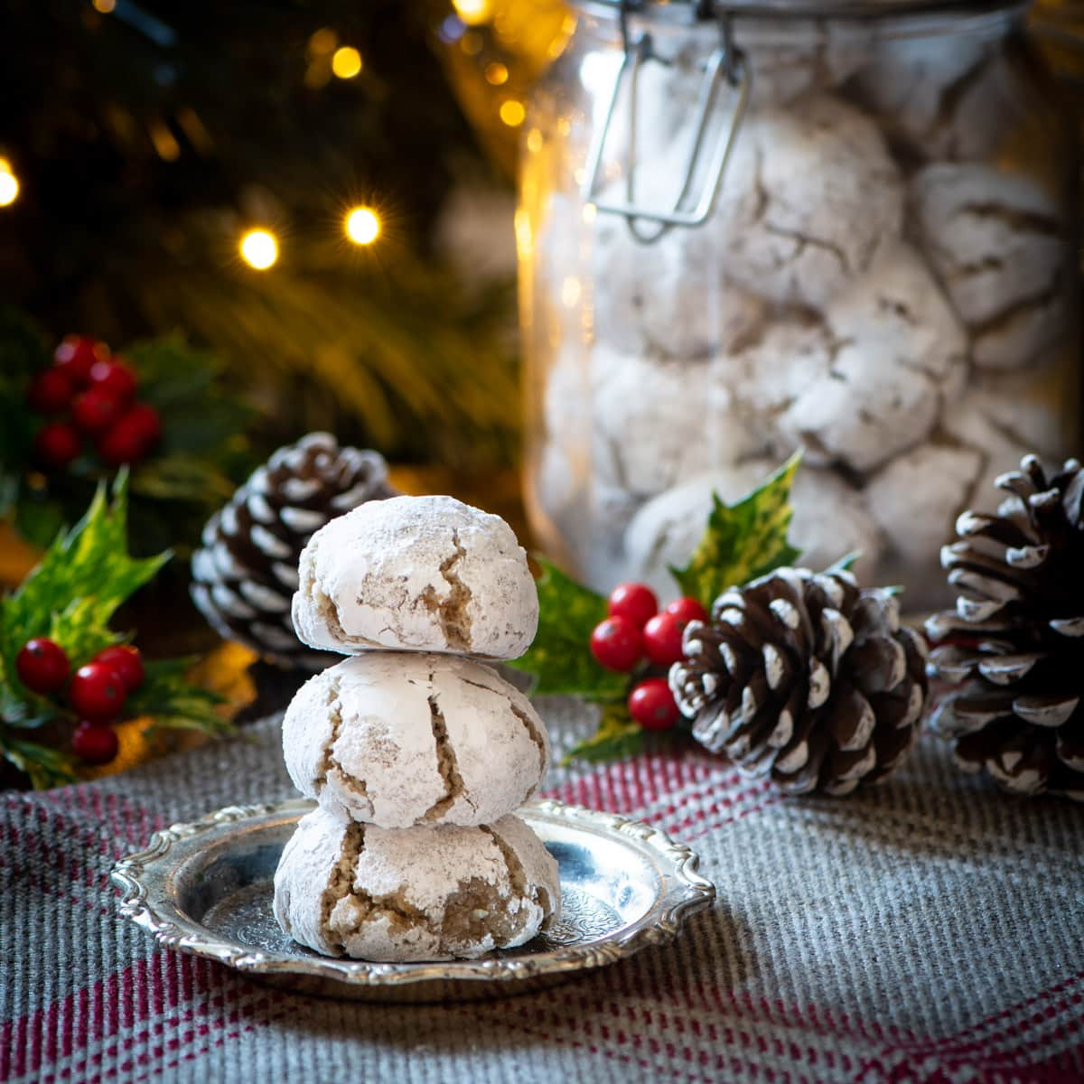 A stack of Christmas amaretti biscuits. There's a jar containing more biscuits in the background. The biscuits are surrounded by twinkling Christmas lights, pine cones and holly.