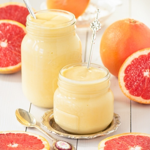 Two jars of grapefruit curd surrounded by cut pink grapefruits