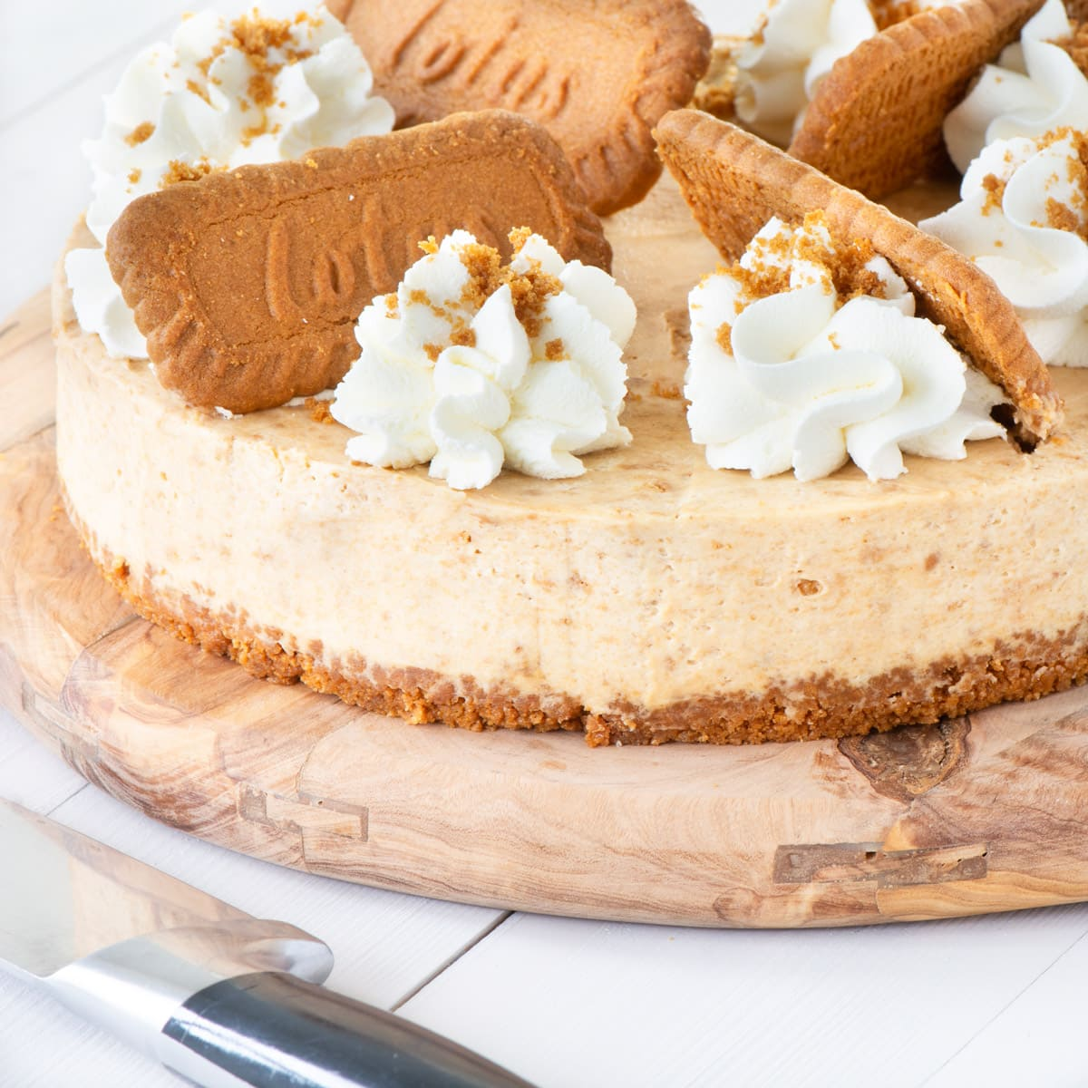 A Biscoff cheesecake on a wooden board. The cheesecake is topped with whipped cream and biscuits. There is a knife in the foreground.