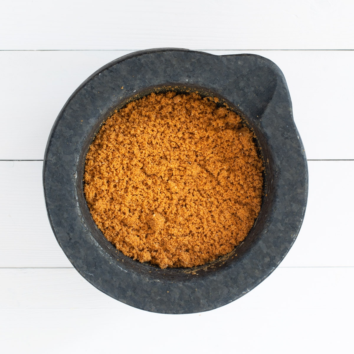 Finely ground Lotus Biscoff Biscuits in a mortar (stone grinding bowl)