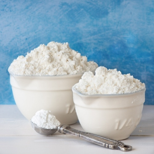 A half cup and a quarter cup of self-raising flour with baking powder on a silver spoon.