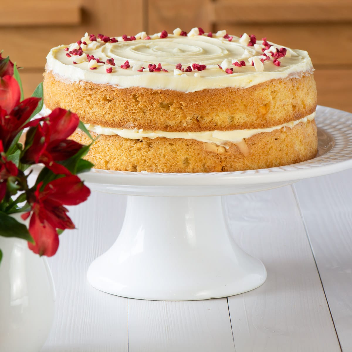 A white chocolate cake on a cake stand.