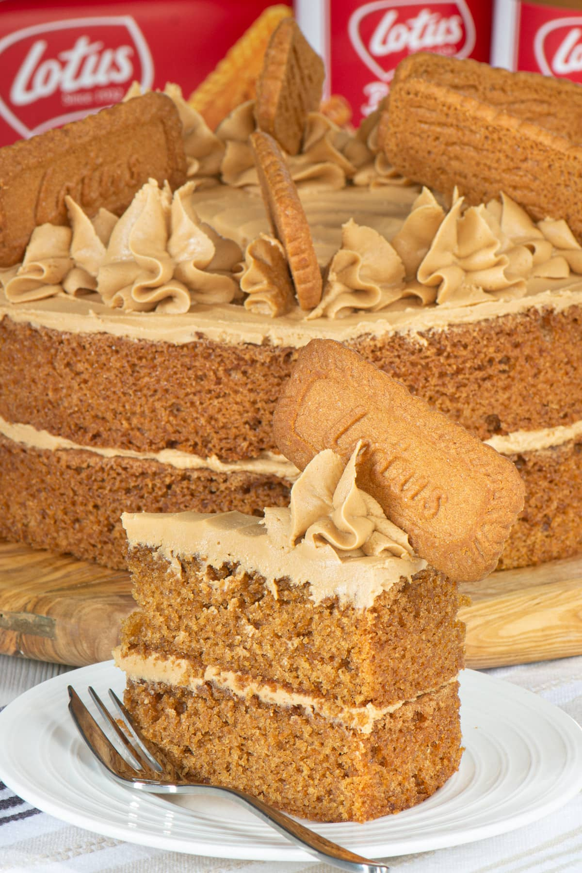 A slice of Biscoff cake with the remaining cake in the background.