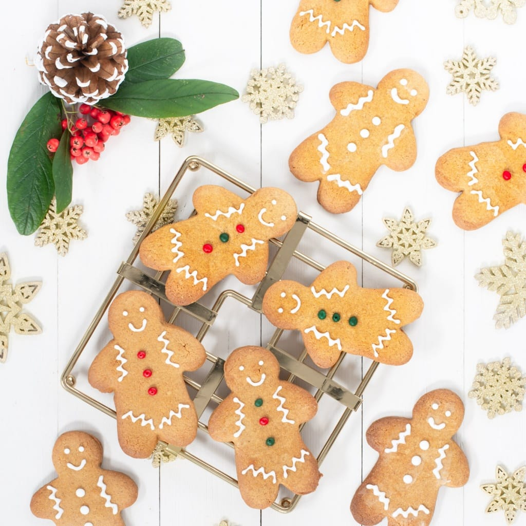 Gingerbread men decorated with royal icing on a wire rack.