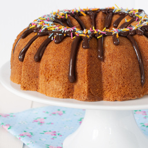 Vanilla bundt cake on a white cake stand.