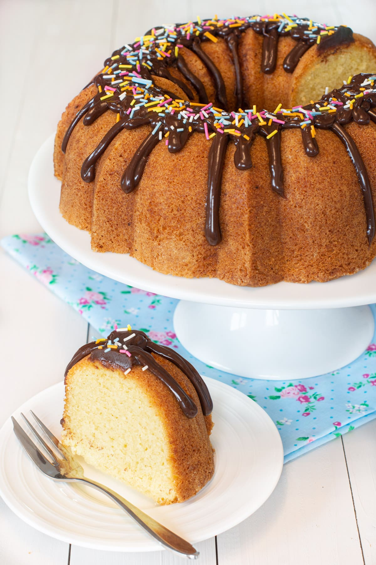 A vanilla bundt cake with chocolate icing and sprinkles. There's a slice remove which is on a plate.
