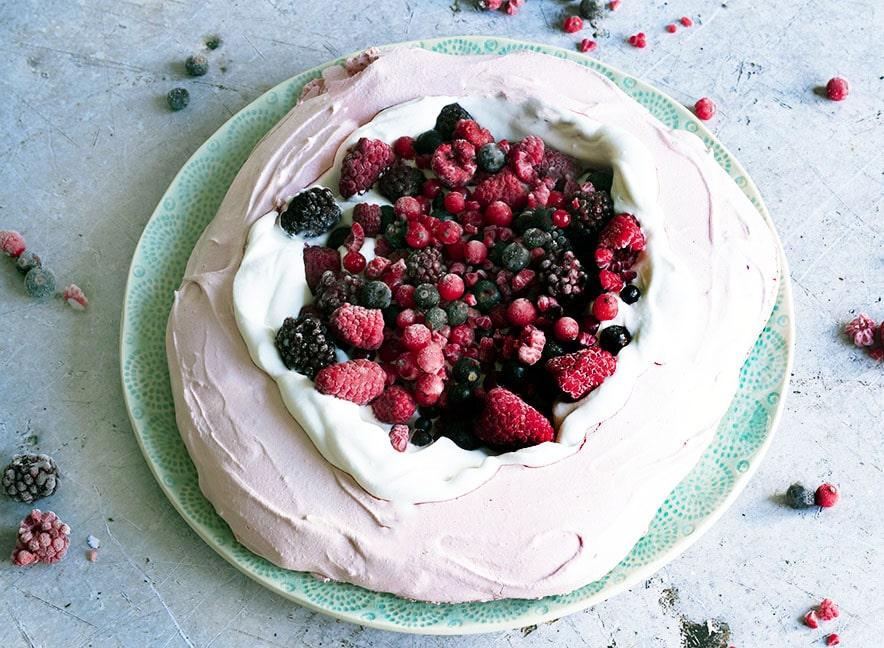Pink vegan pavlova topped with whipped coconut cream and berries.