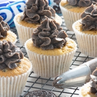 Oreo cupcakes topped with Oreo buttercream and Oreo buttercream in a piping bag.
