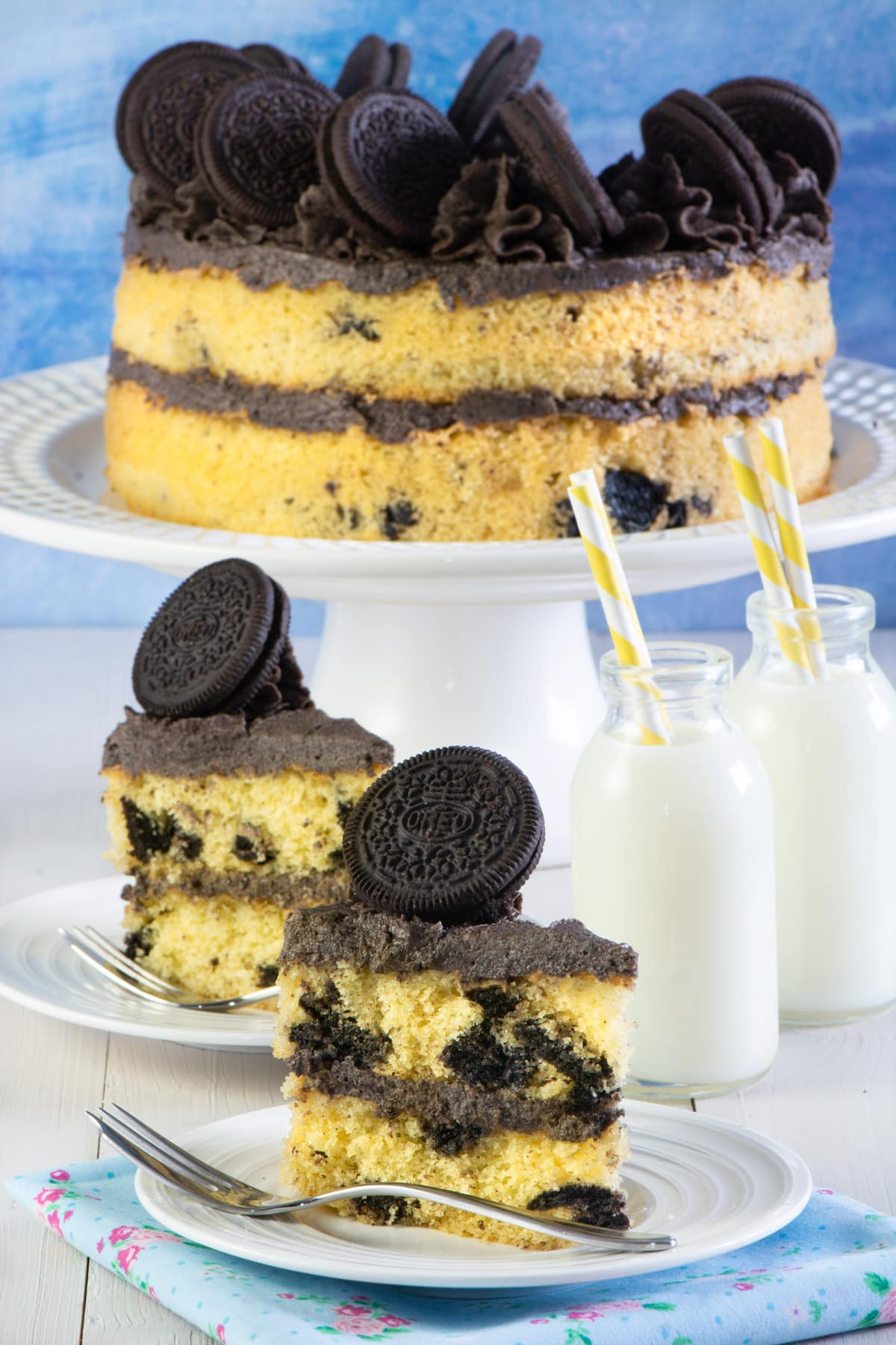 Oreo cake on a stand with 2 slices on plates.