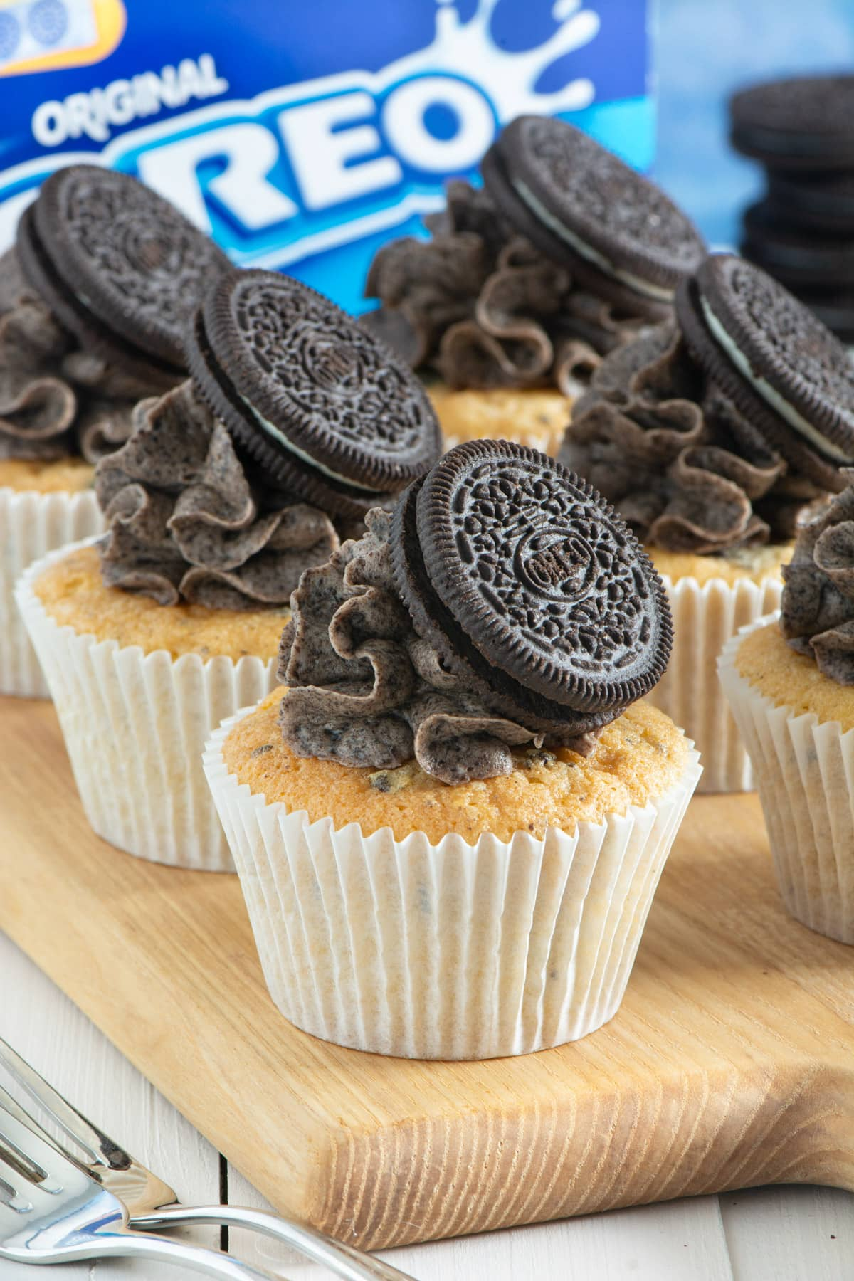 Decorated oreo cupcakes on a wooden board.