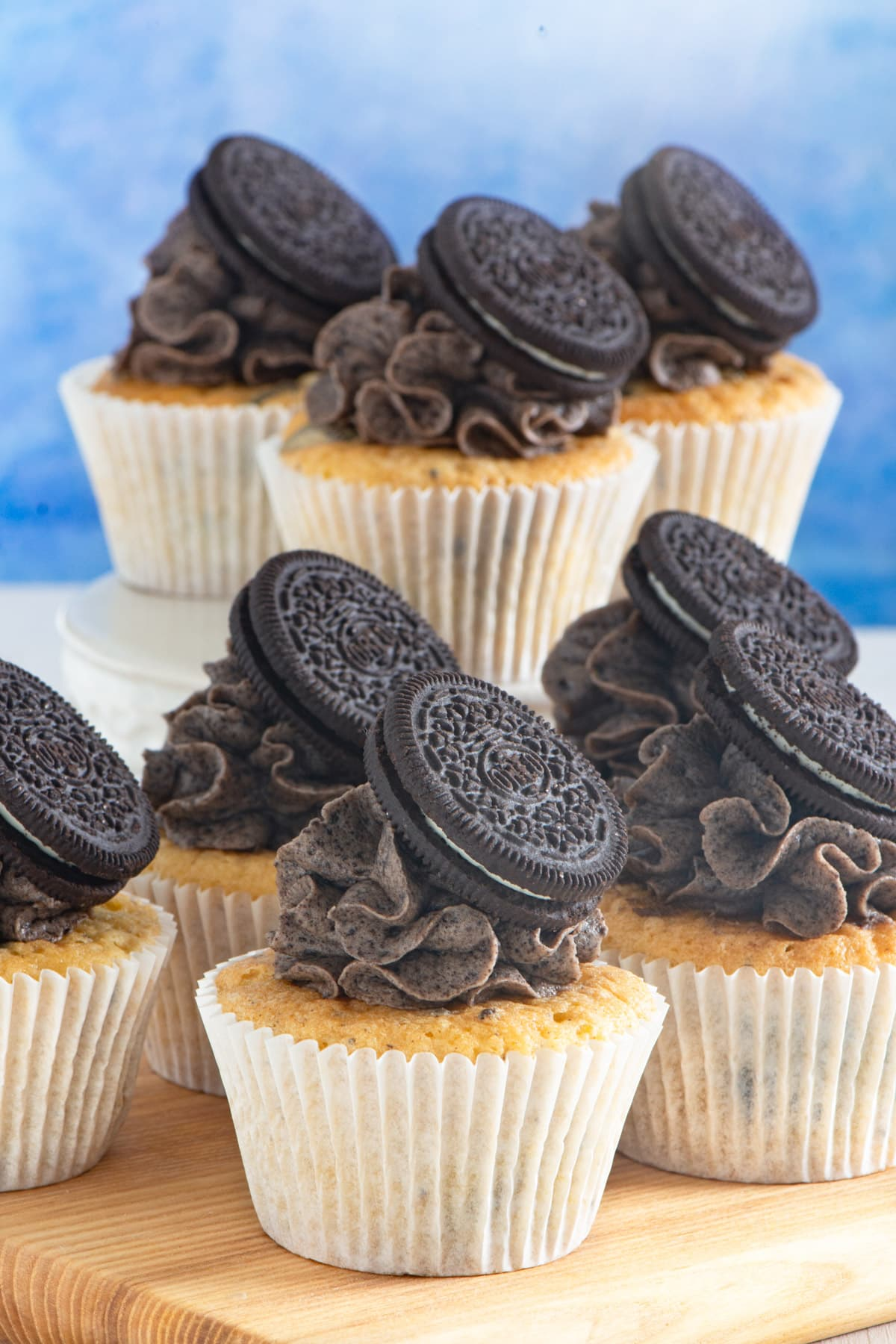 Decorated oreo cupcakes on a board and on a cake stand behind.