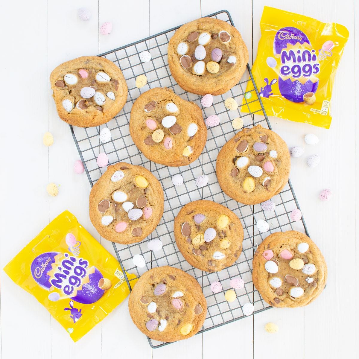 Mini egg cookies on a cooling rack with packets of mini eggs.