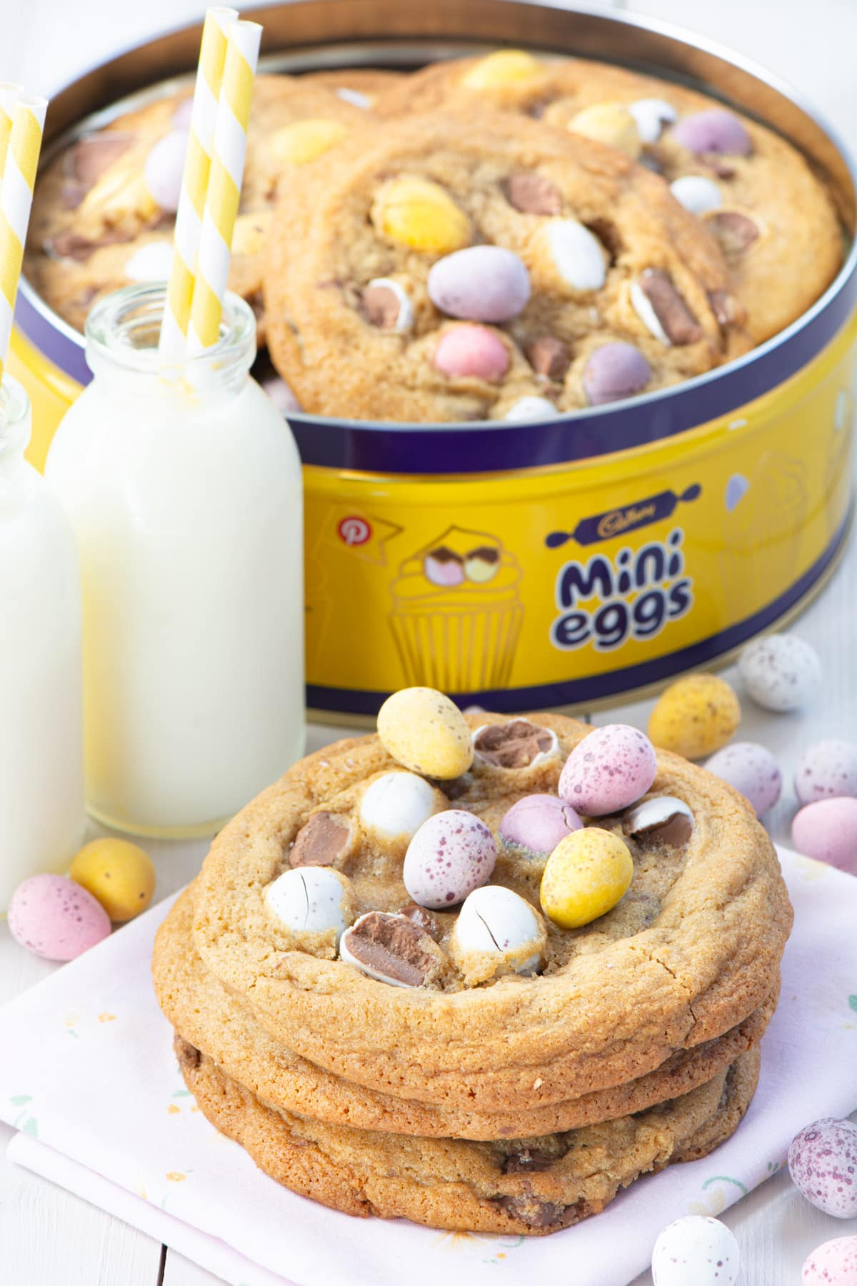Mini egg cookies stack with milk and more in a mini egg branded tin.
