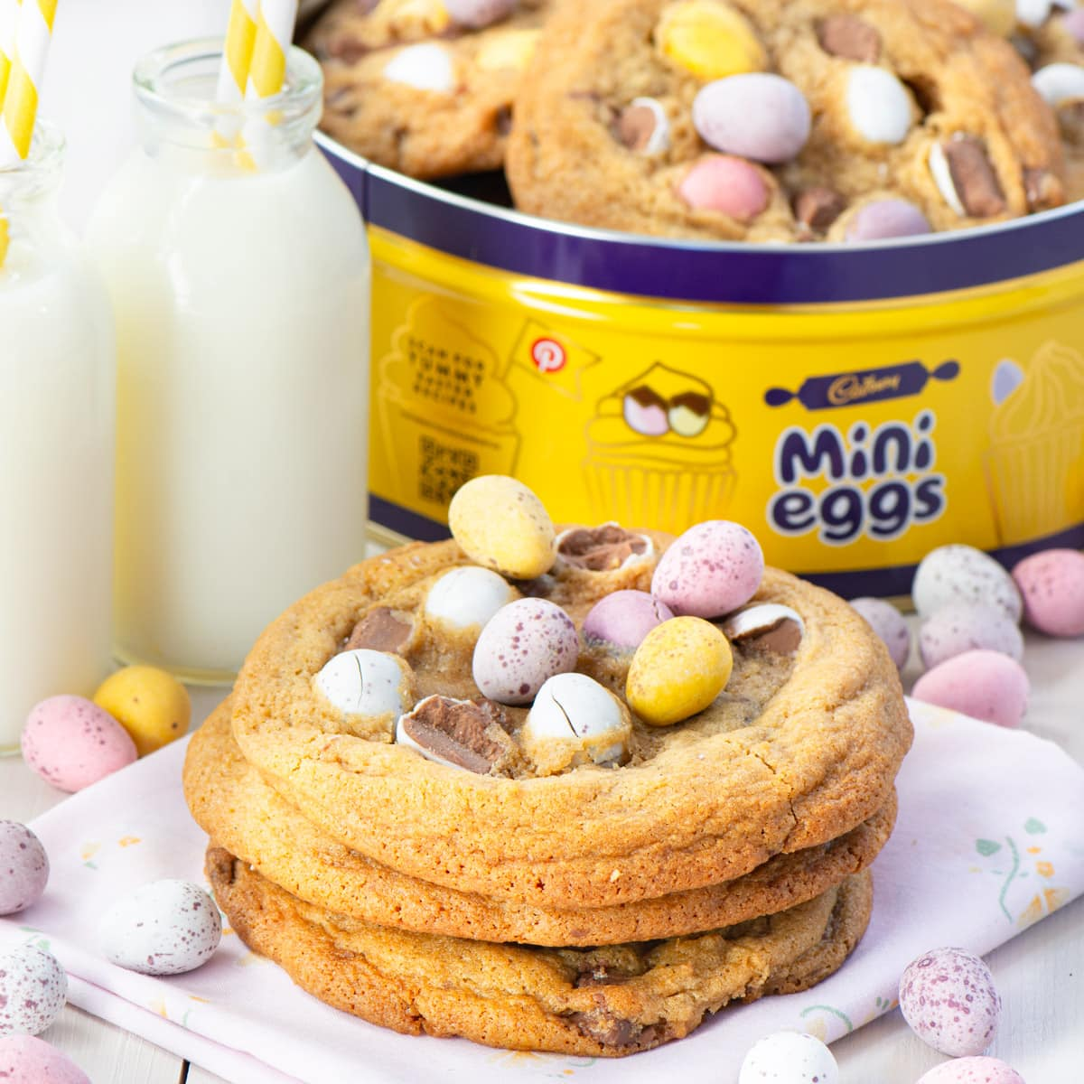 Mini egg cookies stacked in front of a mini egg tin with more cookies.