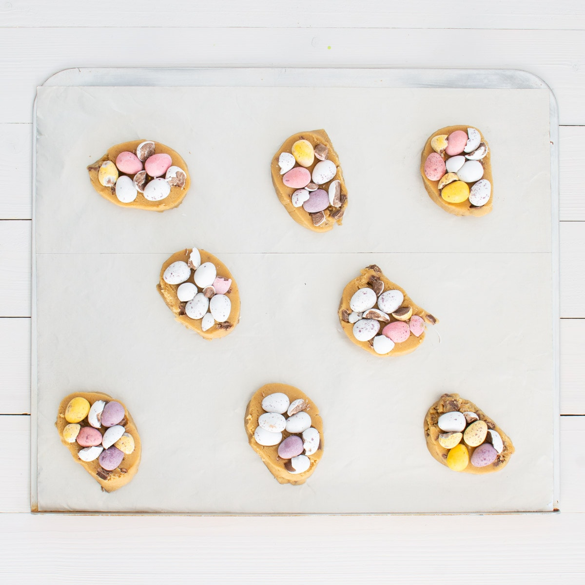 Unbaked mini egg cookies on a baking sheet with lots of mini eggs piles on top the dough.
