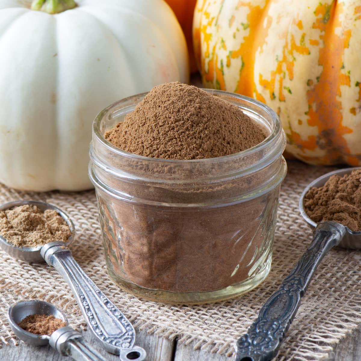 View of a small jar of pumpkin spice with the contents protruding from the top with spoons filled with the ingredients in the front and pumpkins in the background.